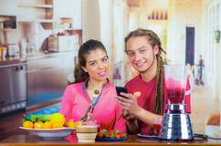 Hispanic young healthy couple enjoying breakfast together, sharing fruits, drinking smoothie and smiling, home kitchen. Background Royalty Free Stock Photos