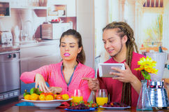 Hispanic young healthy couple enjoying breakfast together, sharing fruits and smiling while looking at tablet screen. Home kitchen background Stock Photography