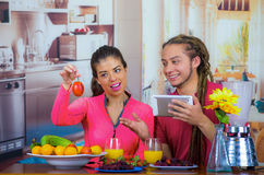 Hispanic young healthy couple enjoying breakfast together, sharing fruits and smiling while looking at tablet screen. Home kitchen background Stock Photos