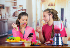 Hispanic young healthy couple enjoying breakfast together, sharing fruits, staring at mobile screen and smiling, home. Kitchen background Stock Photo
