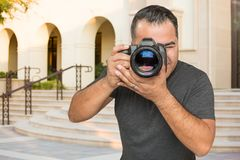 Hispanic Young Male Photographer With DSLR Camera Outdoors. In Front of a Building stock photos
