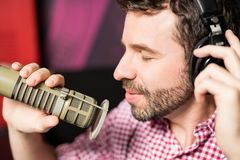 Hispanic young man recording a song in radio studio. Close up of hispanic young man with headphones recording a song with professional microphone in radio studio Royalty Free Stock Photography