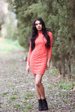 Hispanic young woman wearing orange dress in urban park Royalty Free Stock Photography