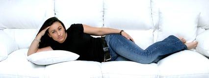 Hispanico bonito atractivo o muchacha española que pone en el pensamiento grande del sofá del cuero blanco.