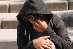 Hispanico preocupado triste 13 años del adolescente de la escuela que plantea la sentada al aire libre en la calle - ascendente c Imagen de archivo
