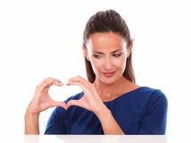 Hispanique attrayant regardant un signe d'amour Photographie stock libre de droits