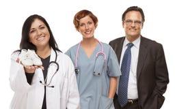 Hispanische Ärztin oder Krankenschwester mit Babyschuhen und Stafff Stockfotografie