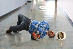 Hispanische Arbeitskraft, die auf Boden fällt Stockfoto