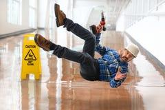 Hispanische Arbeitskraft, die auf nassen Boden fällt Stockfotos