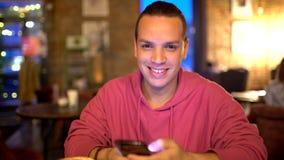 Hispanische Ethnie-junger Mann, der Handy an der gemütlichen Kaffeestube verwendet Porträt der attraktiven lächelnden hispanische stock video footage
