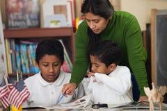 Hispanische Familie in der Hausunterricht-Einstellung Felsen studierend Stockfotografie
