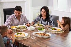 Hispanische Familie, die bei Tisch Mahlzeit genießt stockbild