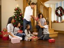 Hispanische Familie, die Geschenke am Weihnachten austauscht Stockbilder