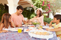 Hispanische Familie, die zu Hause Mahlzeit im Freien zusammen genießt lizenzfreies stockbild