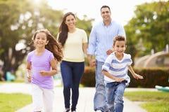 Hispanische Familie, die zusammen in Park geht Lizenzfreie Stockfotos