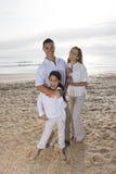 Hispanische Familie mit dem kleinen Mädchen, das auf Strand steht stockbilder