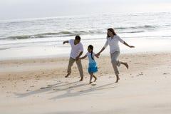 Hispanische Familienholdinghände, die auf Strand überspringen stockbild