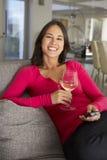 Hispanische Frau auf Sofa Watching Fernsehtrinkendem Wein Stockfotografie