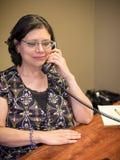 Hispanische Frau bei der Arbeit, die Schreibtisch-Arbeit erledigt stockfoto