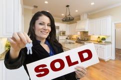 Hispanische Frau in der Küche, die Haus-Schlüssel und Verkaufszeichen hält Lizenzfreie Stockbilder