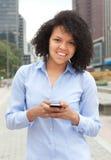 Hispanische Frau in der Stadt, die Mitteilung mit Telefon sendet Lizenzfreies Stockfoto