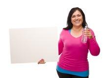 Hispanische Frau in der Trainings-Kleidung mit unbelegtem Zeichen Stockfoto