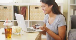 Hispanische Frau, die einen Kauf on-line abschließt Stockbild