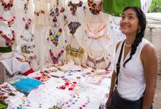 Hispanische Frau, die gestickte mexikanische Blusen bewundert Lizenzfreie Stockfotos