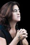 Hispanische Frau, die mit ihren Augen geschlossen betet Stockbilder