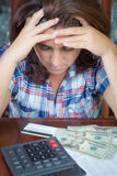 Hispanische Frau, die zu Hause Geld zählt, um die Wechsel einzulösen Stockfoto