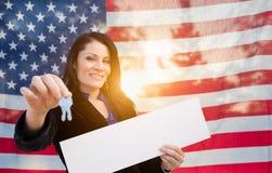 Hispanische Frau hält Haus-Schlüssel und leeres Zeichen vor amerikanischer Flagge stockfotografie