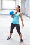 Hispanische Frau im blauen Sport bekleiden das Demonstrieren der sauberen Haltung mit einem blauen kettlebell, im Freien Lizenzfreies Stockbild