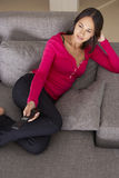 Hispanische Frau im Sofa Watching Fernsehen Stockbild