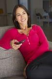 Hispanische Frau im Sofa Watching Fernsehen Lizenzfreies Stockfoto