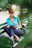 Hispanische Frau mit digitalem Tablette-PC auf Bank Stockfotografie
