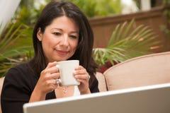 Hispanische Frau mit Kaffee und Laptop Stockbilder
