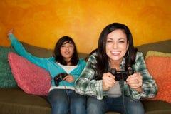 Hispanische Frau und Mädchen, die Videospiel spielt Lizenzfreie Stockfotografie
