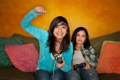 Hispanische Frau und Mädchen, die Videospiel spielt Lizenzfreies Stockbild