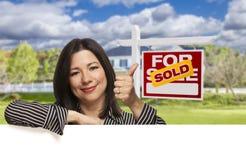 Hispanische Frau vor verkauft für Verkaufs-Zeichen, Haus lizenzfreies stockbild