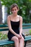 Hispanische Jugendliche mit einem romantischen Blick, der auf einem Park sitzt Lizenzfreies Stockfoto