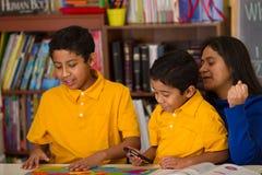 Hispanische Jungen mit Mutter in der Schulumgebung Lizenzfreies Stockfoto