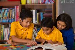 Hispanische Jungen mit Mutter in der Schulumgebung Lizenzfreie Stockfotos