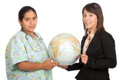 Hispanische Krankenschwester und Lehrer, welche die Welt anhält Lizenzfreies Stockfoto