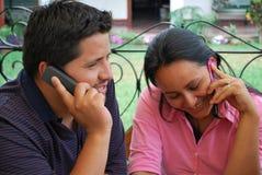 Hispanische Kursteilnehmer, die auf ihren Mobiltelefonen sprechen Lizenzfreie Stockfotos