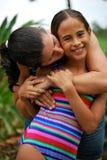Hispanische Mutter, die ihre Tochter küßt Lizenzfreies Stockfoto