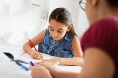Hispanische Mutter-helfendes Mädchen, das zu Hause Schulhausarbeit tut lizenzfreie stockbilder