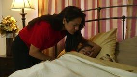 Hispanische Mutter neigt liebevoll zu ihrer kleinen Tochter, die krank ist stock video footage
