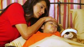 Hispanische Mutter neigt liebevoll zu ihrer kleinen Tochter, die krank ist stock footage