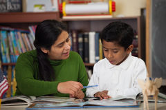 Hispanische Mutter und Junge in der Hausunterricht-Einstellung Felsen studierend Stockfotografie