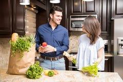 Hispanische Paare, welche die Einkaufstüte in der Küche leeren lizenzfreie stockbilder